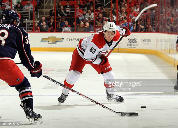 Boone Jenner of the Columbus Blue Jackets skates in front of Jeff Skinner of the Carolina Hurricanes who winds up to take a shot during their NHL...