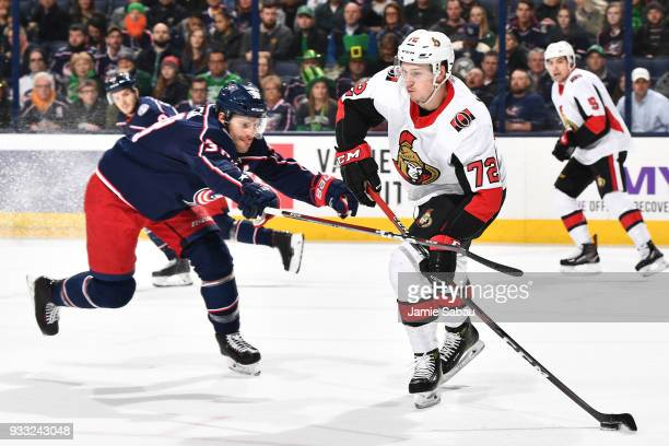 Boone Jenner of the Columbus Blue Jackets sticks checks Thomas Chabot of the Ottawa Senators in the first period as Chabot starts a breakout on March...