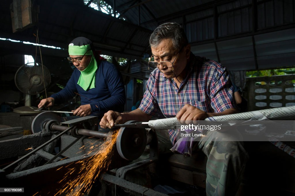 Boonsoung Sittipaisal, right, sharpens a sword's blade at his workshop on December 19, 2017 in Lampang, Thailand. The craft of sword making is dying in Thailand and Boontan Sittipaisal is one of the country's remaining people who are still making the dah, a Burmese word that means 'blade', which represents a long history of sword making across Indochina. The single-edged sword stretches out from a round handle with a subtle curve that widens toward the tip and was used in Thailand during the Ayutthaya period as weapons but later incorporated into ceremonial dances, physical education classes, and martial arts. Boontan, his brother Boonsoung, and a team of craftsmen finish about ten swords each day at their workshop located at the suburb of Hang Chat in Lampang, forging the swords by hand while paying attention to quality and passing on the endangered art to the next generation in hopes that it will not die.