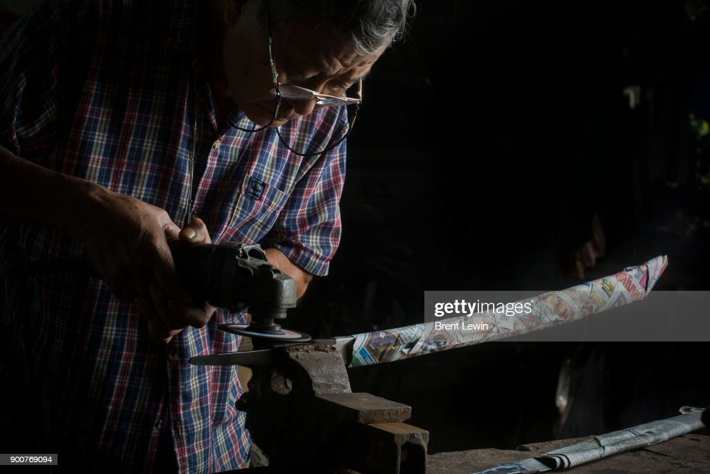 Boonsoung Sittipaisal sands a sword at his workshop on December 19, 2017 in Lampang, Thailand. The craft of sword making is dying in Thailand and Boontan Sittipaisal is one of the country's remaining people who are still making the dah, a Burmese word that means 'blade', which represents a long history of sword making across Indochina. The single-edged sword stretches out from a round handle with a subtle curve that widens toward the tip and was used in Thailand during the Ayutthaya period as weapons but later incorporated into ceremonial dances, physical education classes, and martial arts. Boontan, his brother Boonsoung, and a team of craftsmen finish about ten swords each day at their workshop located at the suburb of Hang Chat in Lampang, forging the swords by hand while paying attention to quality and passing on the endangered art to the next generation in hopes that it will not die.