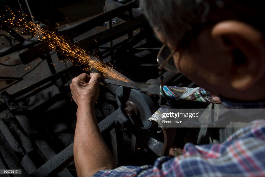 Boonsoung Sittipaisal sharpens a sword's blade at his workshop on December 19, 2017 in Lampang, Thailand. The craft of sword making is dying in Thailand and Boontan Sittipaisal is one of the country's remaining people who are still making the dah, a Burmese word that means 'blade', which represents a long history of sword making across Indochina. The single-edged sword stretches out from a round handle with a subtle curve that widens toward the tip and was used in Thailand during the Ayutthaya period as weapons but later incorporated into ceremonial dances, physical education classes, and martial arts. Boontan, his brother Boonsoung, and a team of craftsmen finish about ten swords each day at their workshop located at the suburb of Hang Chat in Lampang, forging the swords by hand while paying attention to quality and passing on the endangered art to the next generation in hopes that it will not die.