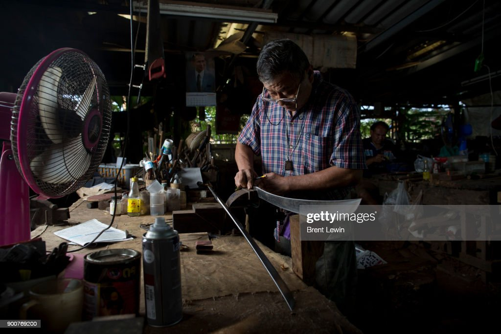 Boonsoung Sittipaisal works on a sword at his workshop on December 19, 2017 in Lampang, Thailand. The craft of sword making is dying in Thailand and Boontan Sittipaisal is one of the country's remaining people who are still making the dah, a Burmese word that means 'blade', which represents a long history of sword making across Indochina. The single-edged sword stretches out from a round handle with a subtle curve that widens toward the tip and was used in Thailand during the Ayutthaya period as weapons but later incorporated into ceremonial dances, physical education classes, and martial arts. Boontan, his brother Boonsoung, and a team of craftsmen finish about ten swords each day at their workshop located at the suburb of Hang Chat in Lampang, forging the swords by hand while paying attention to quality and passing on the endangered art to the next generation in hopes that it will not die.