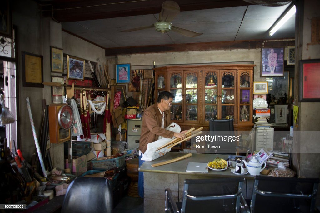 Boontan Sittipaisal handles sword holders at his office on December 19, 2017 in Lampang, Thailand. The craft of sword making is dying in Thailand and Boontan Sittipaisal is one of the country's remaining people who are still making the dah, a Burmese word that means 'blade', which represents a long history of sword making across Indochina. The single-edged sword stretches out from a round handle with a subtle curve that widens toward the tip and was used in Thailand during the Ayutthaya period as weapons but later incorporated into ceremonial dances, physical education classes, and martial arts. Boontan, his brother Boonsoung, and a team of craftsmen finish about ten swords each day at their workshop located at the suburb of Hang Chat in Lampang, forging the swords by hand while paying attention to quality and passing on the endangered art to the next generation in hopes that it will not die.