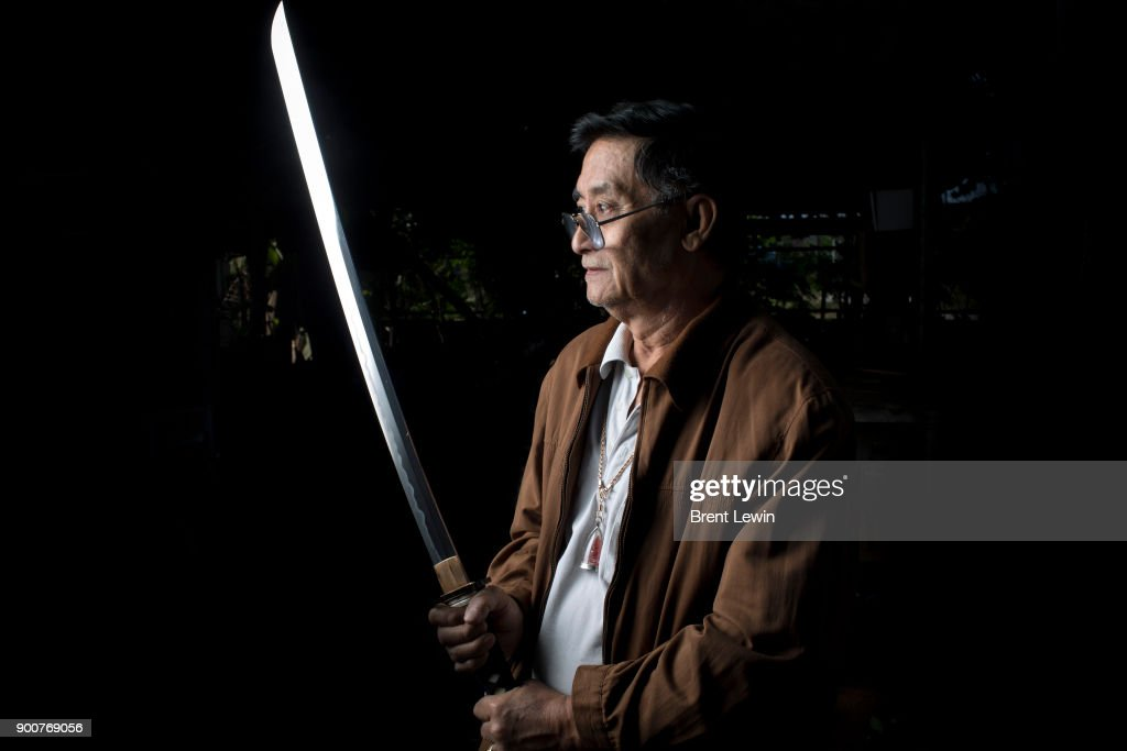 Boontan Sittipaisal poses for a photograph with a sword at his workshop on December 19, 2017 in Lampang, Thailand. The craft of sword making is dying in Thailand and Boontan Sittipaisal is one of the country's remaining people who are still making the dah, a Burmese word that means 'blade', which represents a long history of sword making across Indochina. The single-edged sword stretches out from a round handle with a subtle curve that widens toward the tip and was used in Thailand during the Ayutthaya period as weapons but later incorporated into ceremonial dances, physical education classes, and martial arts. Boontan, his brother Boonsoung, and a team of craftsmen finish about ten swords each day at their workshop located at the suburb of Hang Chat in Lampang, forging the swords by hand while paying attention to quality and passing on the endangered art to the next generation in hopes that it will not die.