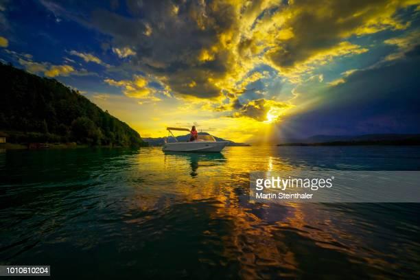 Boot am See im Sonnenuntergang und dramatischen Himmel