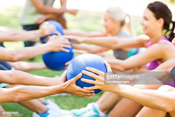 bootcamp class exercising with medicine balls in park - passing sport stock pictures, royalty-free photos & images