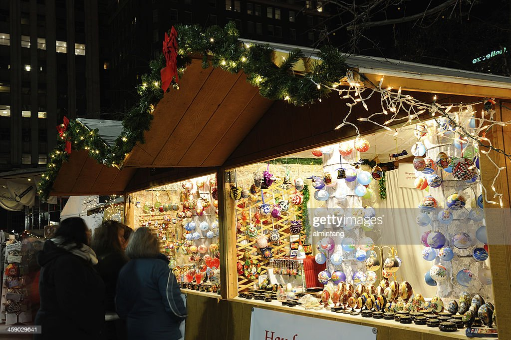 'Philadelphia, USA - December 14, 2012. Shoppers at vendor booths in Christmas Village at night in downtown Philadelphia. Christmas Village in Philadelphia is a holiday tradition modeled after German Christmas Markets which dates back to the late Middle Ages. It is located at Love Park and runs from November 22nd to December 24th. Over 60 vendors sell their goods in timber booths which are decorated with holiday lights. It attracts a lot of visitors shopping for holiday items, enjoying variety of foods and live performance of Christmas music.'