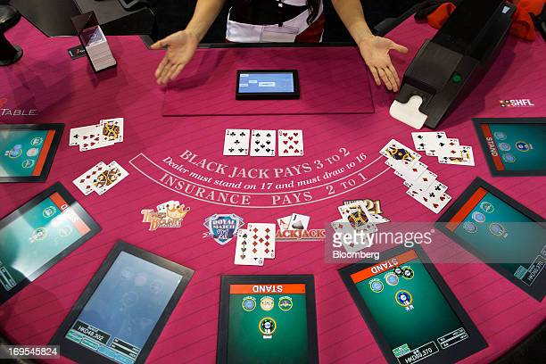 A booth attendant performs a demonstration at an electronic blackjack table during the Global Gaming Expo Asia event in Macau China on Thursday May...