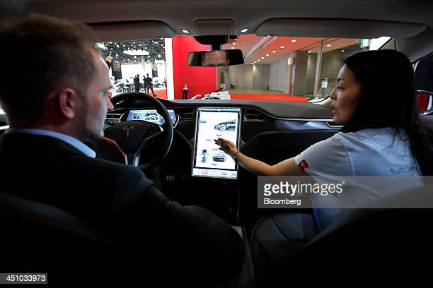 A booth attendant right explains the interior functions of a Tesla Motors Inc Model S electric vehicle to an attendee at the 43rd Tokyo Motor Show...
