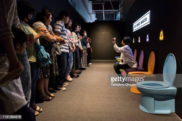 A booth attendant sits on a toilet bowl as she briefs visitors at the Unko Museum Yokohama on May 24 2019 in Yokohama Japan The temporary popup...