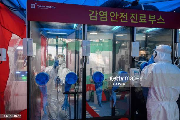 Booth is disinfected as a nurse speaks to a woman during a COVID-19 novel coronavirus test at a testing booth outside Yangji hospital in Seoul on...