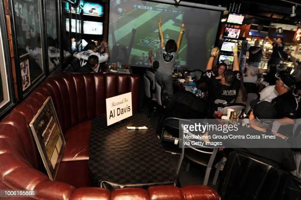 A booth reserved for Al Davis sits vacant as the Oakland Raiders Houston Texans game flashes on the screen during the second half at Ricky's Sports...