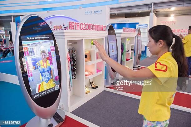 A booth staffer tries on clothing in front of V30 Nshow 3D Dressing Mirror during the ChinaNortheast Asian Expo at Changchun International Conference...