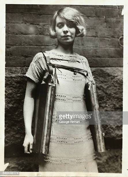 Bootlegger recently arrested in Cincinnati had this novel device strapped around him for carrying his stock of wet goods. Photo shows a young lady...