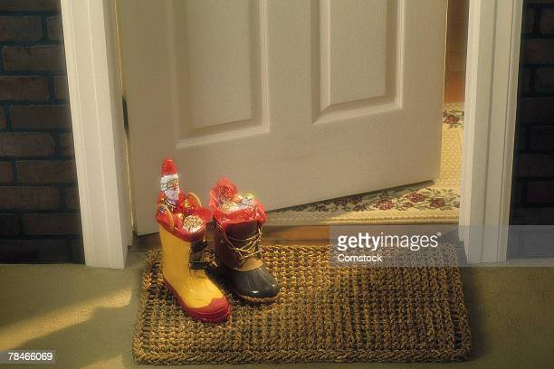 boots filled with candy on door mat - stiefel stock-fotos und bilder