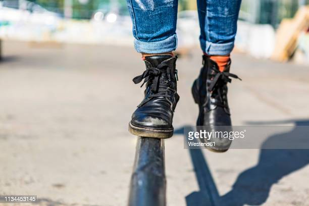 boots of a woman balancing on rail - black boot stock pictures, royalty-free photos & images