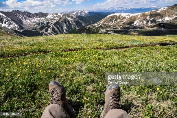 boots of man sitting in field on mountain at loveland pass, colorado - front range mountain range stock pictures, royalty-free photos & images