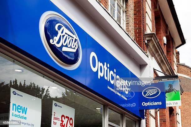 boots opticians shop signs - ankle boot stock photos and pictures