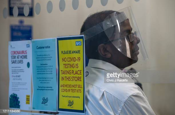 Boots pharmacy employee wears a face shield whilst working in an open store which has signs in the window warning of the lack of covid-19 testing in...