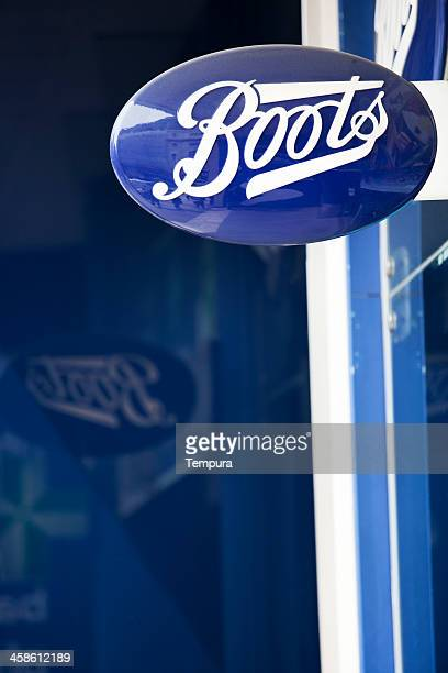 boots pharmacy logo on blue wall. - ankle boot stock photos and pictures