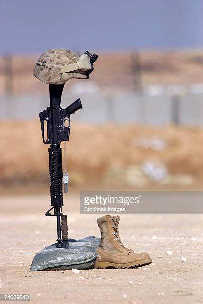 boots, rifle, dog tags, and helmet stand in solitude to honor fallen soldiers during a service held at al asad air base, iraq february 18, 2006. - boots rifle helmet stock pictures, royalty-free photos & images