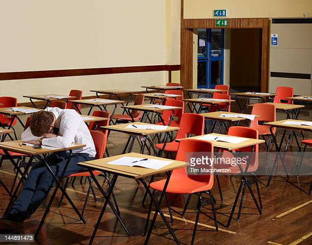 booy asleep in a school hall - desk stock pictures, royalty-free photos & images