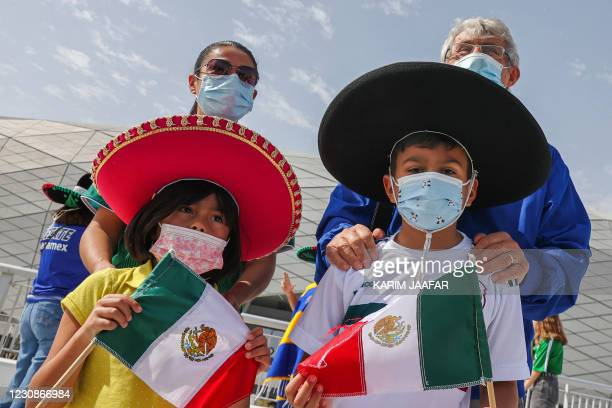 Bora Milutinovic , the Serbian coach who led Mexico to the quarter-finals at the 1986 FIFA World Cup, poses behind children while mask-clad due to...