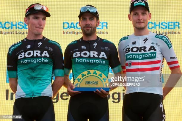 BoraHansgrohe's Polish cyclist Rafal Majka German cyclist Michael Schwarzmann and Austrian Lukas Postlberger pose on the podium with the leader...