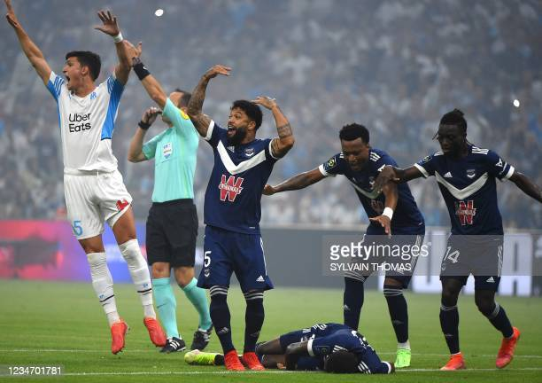 Bordeaux and Marseille' players call for the medic as Bordeaux's Nigerian forward Samuel Kalu lays on the ground playersduring the French L1 football...