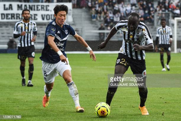 Bordeaux' Corean forward Hwang Ui-jo fights for the ball with Angers's French forward Sada Thioub during the French L1 football match between Angers...