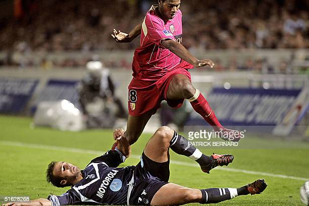 Bordeaux's midfielder Marc Planus tackles Lens's midfielder Olivier Thomert during their French L1 football match 30 October 2004 at the Chaban...