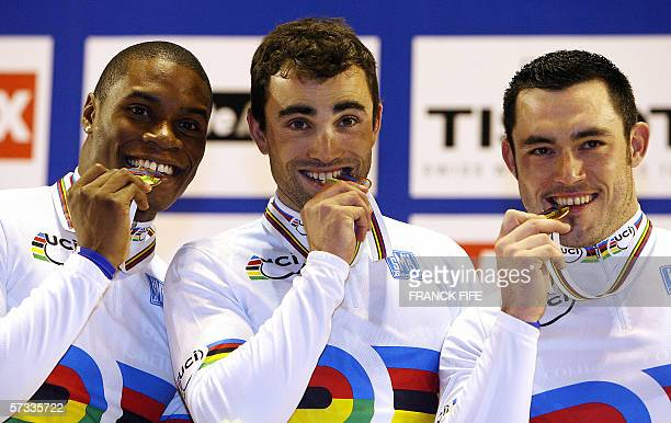 French riders Gregory Bauge, Mickael Bourgain and Arnaud Tournant bite their gold medal on the podium after they won the men's team sprint final...