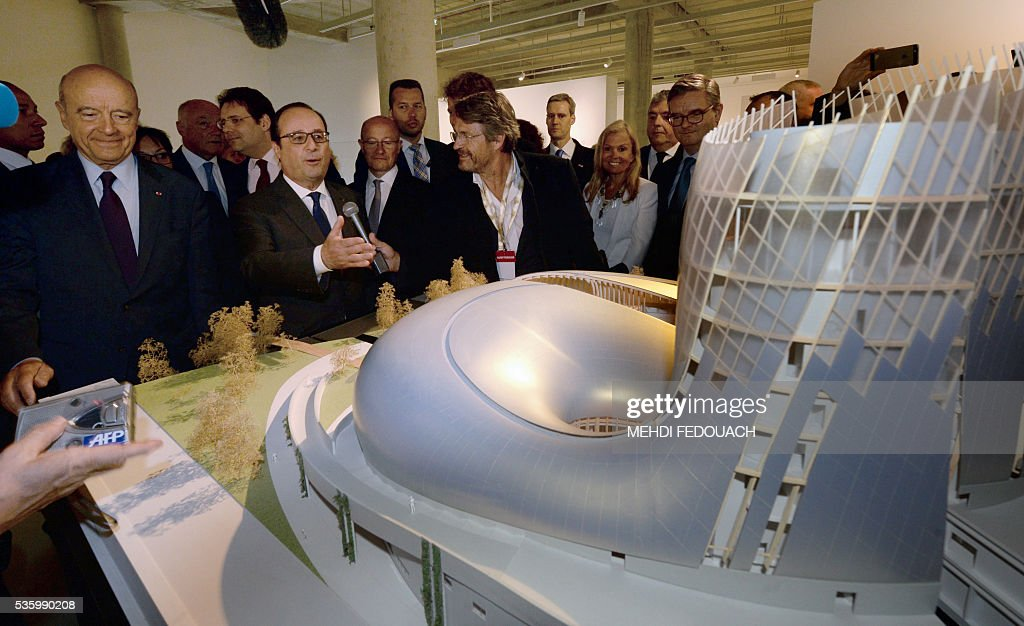 Bordeaux mayor Alain Juppe (L) and French President Francois Hollande (C) view a model of the Cite du Vin (Wine Museum) during the museum's inauguration on May 31, 2016 in Bordeaux. New cultural, touristic and architectural symbol of Bordeaux, the Wine Museu wishes to attract 450,000 visitors per year, is set to open on June 1 following its inauguration by Francois Hollande. / AFP / POOL / MEHDI