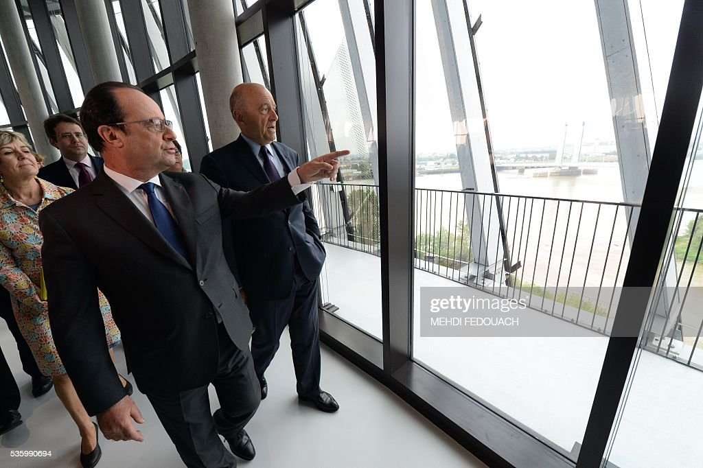 Bordeaux mayor Alain Juppe (R) and French President Francois Hollande tour the Cite du Vin (Wine Museum) during its inauguration on May 31, 2016 in Bordeaux. New cultural, touristic and architectural symbol of Bordeaux, the Wine Museu wishes to attract 450,000 visitors per year, is set to open on June 1 following its inauguration by Francois Hollande. / AFP / POOL / MEHDI