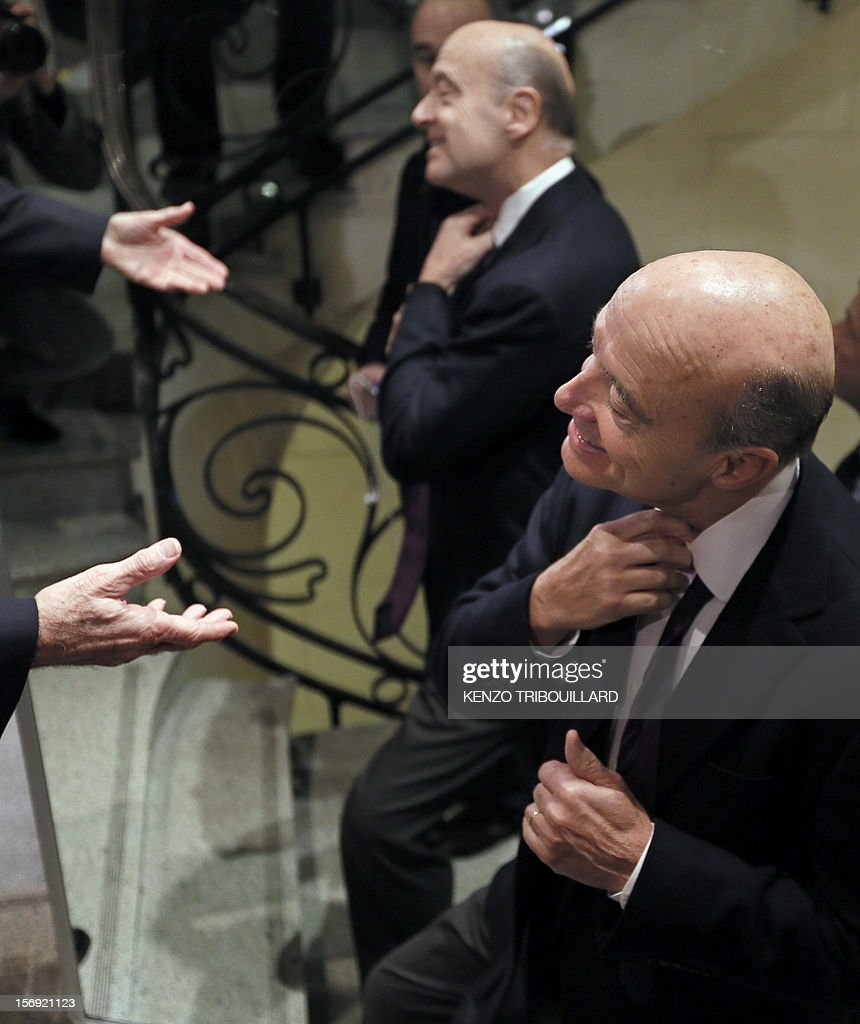 Bordeaux mayor and founder of the French opposition right-wing UMP party, Alain Juppe, adjusts his tie upon his arrival on November 25, 2012, at the headquarters of French radio station Europe 1 in Paris to participate in the 'Le Grand Rendez-Vous' program. Party heavyweight Juppe, a former premier and foreign minister, will hold a mediation meeting later in the day with the right-winger, who was declared the winner of November 22 knife-edge vote to pick a party leader, Jean-Francois Cope, and his centrist rival Francois Fillon. The talks are to establish who actually won the leadership and whether mutual allegations of ballot rigging have any foundation.