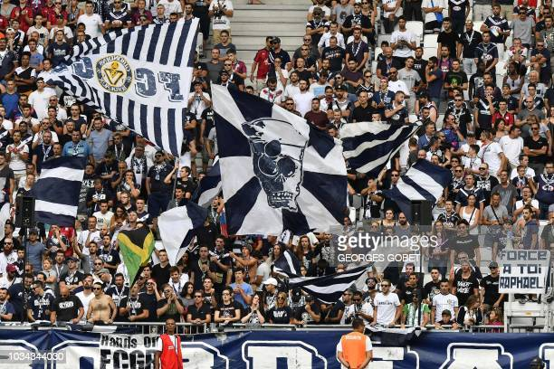 Bordeaux' supporters wave flag as they cheer their team during the French L1 football match between FC Girondins de Bordeaux and Nimes Olympique on...