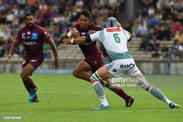 BordeauxBegles' Australian centre Ulupano Seuteni is tackled by Pau's Ben Mowen Australian flanker during the French Top 14 rugby union match between...