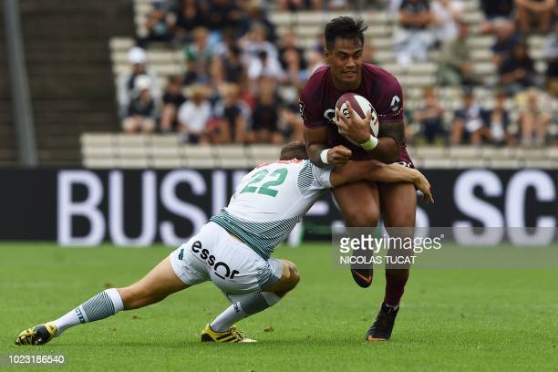 BordeauxBegles' Australian centre Ulupano Seuteni is tackled by Pau's New Zealander fullback Tom Taylor during the French Top 14 rugby union match...