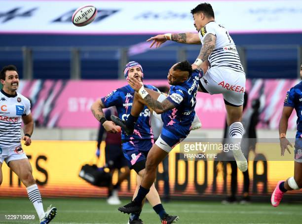 Bordeaux-Begles' New Zealander wing Ben Lam jumps for the ball with Stade Francais' Tongan full-back Telusa Veainu during the French Top 14 rugby...