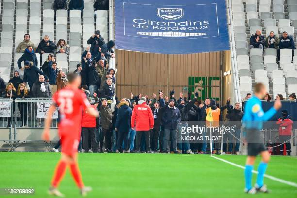 Bordeaux's fans gesture on the pitch as the game is stopped during the French L1 football match between FC Girondins de Bordeaux and Nimes at the...