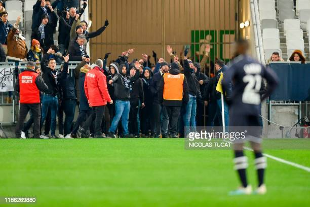 Bordeaux's fans stand on the pitch as the game is stopped during the French L1 football match between FC Girondins de Bordeaux and Nimes at the...