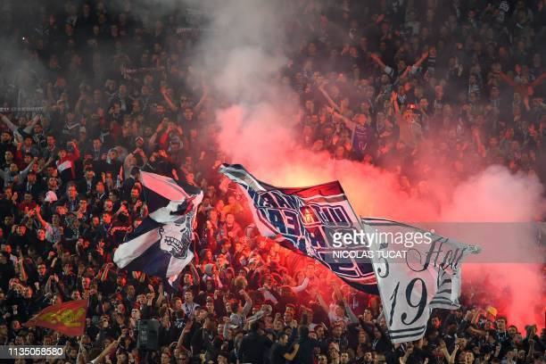 Bordeaux's fans wave flags and light flares during the French Ligue 1 football match between FC Girondins de Bordeaux and Olympique de Marseille at...