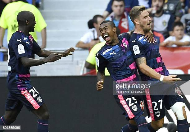 Bordeaux's French defender Gregory Sertic is congratulated by teammates Youssouf Sabaly and Malcom after scoring a goal during the French L1 football...