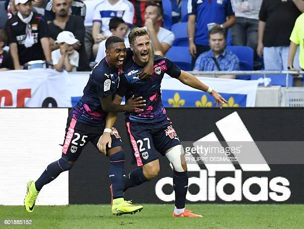 Bordeaux's French defender Gregory Sertic is congratulated by teammate Malcom after scoring a goal during the French L1 football match Olympique...