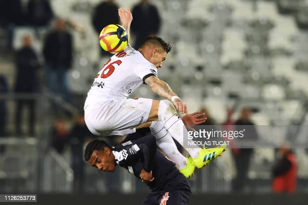 Bordeaux's French defender Jules Kounde vies with Guingamp's French forward Nolan Roux top during the French L1 football match between Bordeaux and...