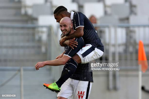 Bordeaux's French defender Nicolas Pallois celebrates with a teammate that he caries on his back after scoring a goal during the French L1 football...