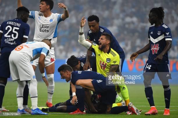 Bordeaux's French goalkeeper Benoit Costil and Bordeaux's French defender Laurent Koscielny call for the medic as Bordeaux's Nigerian forward Samuel...