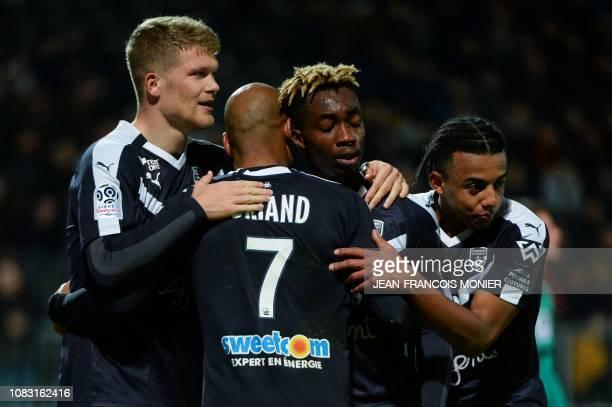Bordeaux's French Ivorian forward Yann Karamoh is congratulated by Bordeaux's French forward Jimmy Briand and Bordeaux's Danish forward Andreas...