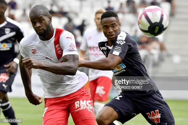 Bordeaux's Guinean forward Francois Kamano vies with Nîmes' French forward Sada Thioub during the French L1 football match between FC Girondins de...