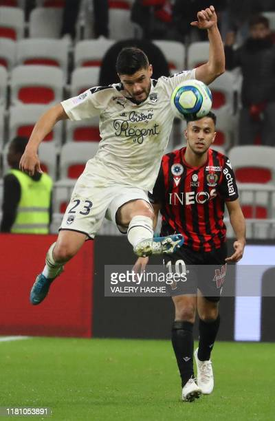 Bordeaux's Swiss defender Loris Benito fights for the ball with Nice's Algerian forward Adam Ounas during the French L1 football match between OGC...